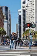 """A couple kisses beside a """"do not cross"""" sign at a crosswalk in downtown San Francisco. Street scene."""