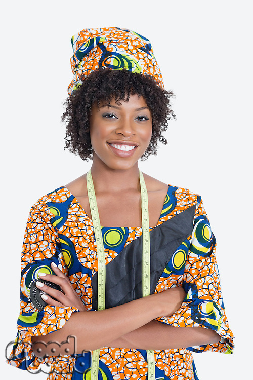 Portrait of young female fashion designer in African print attire standing hands folded over gray background