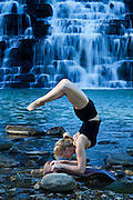Woman practices yoga balancing on a rock by a waterfall.