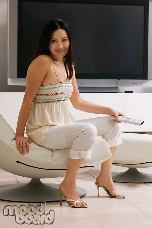 Woman with Remote Control next to Big Screen Television