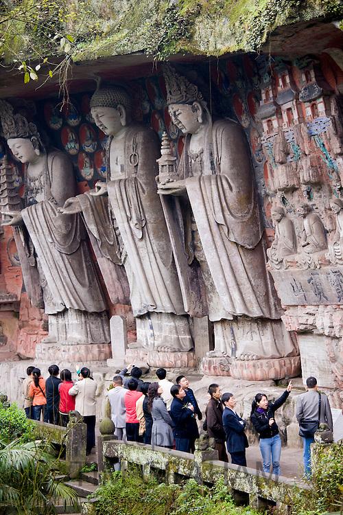Tourists at Dazu rock carvings of Buddha of Great Sunlight, Buddha of Mercy at Mount Baoding, China