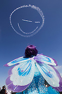 A performer dressed as a fairy watching as a sky-drawn smiley-faced in the sky during Los Angeles County Air Show in Lancaster, California on March 21, 2015. (Photo by Ringo Chiu/PHOTOFORMULA.com)
