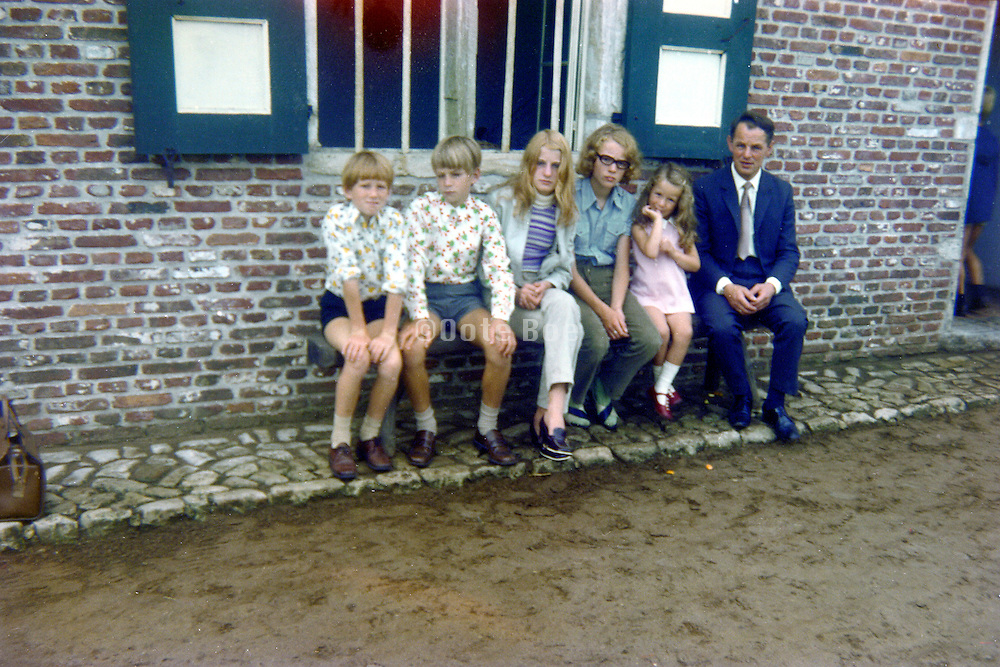 father with five children in front of a an old restored farmhouse 1960s Holland