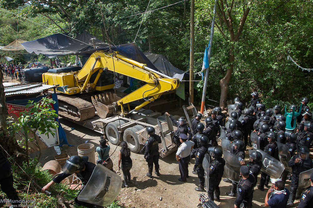 Riot police escort an excavator as they forcibly introduce heavy machinery into the El Tambor mine by violently evicting the local population in peaceful resistance. After two years and two months of peacefully blocking the entrance to U.S.-based Kappes, Cassiday & Associates (KCA) El Tambor gold mine, local residents of San Jose del Golfo and San Pedro Ayampuc were violently evicted by Guatemalan Police forces in order to introduce heavy machinery inside the industrial site. La Puya, San Pedro Ayampuc, Guatemala. May 23, 2014.
