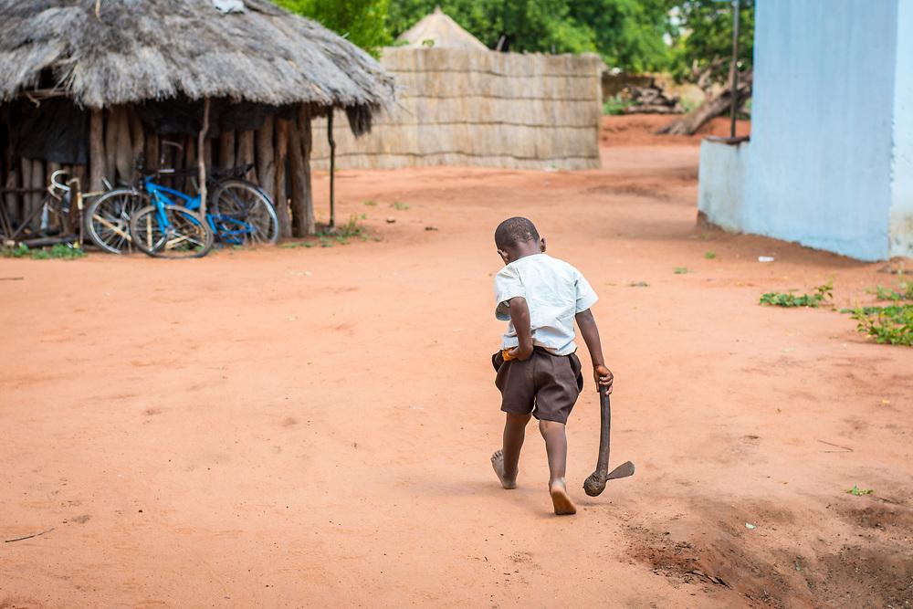 Young Zambian boy walks away through village while holding onto hatchet and his pants, Mukuni Village, Zambia
