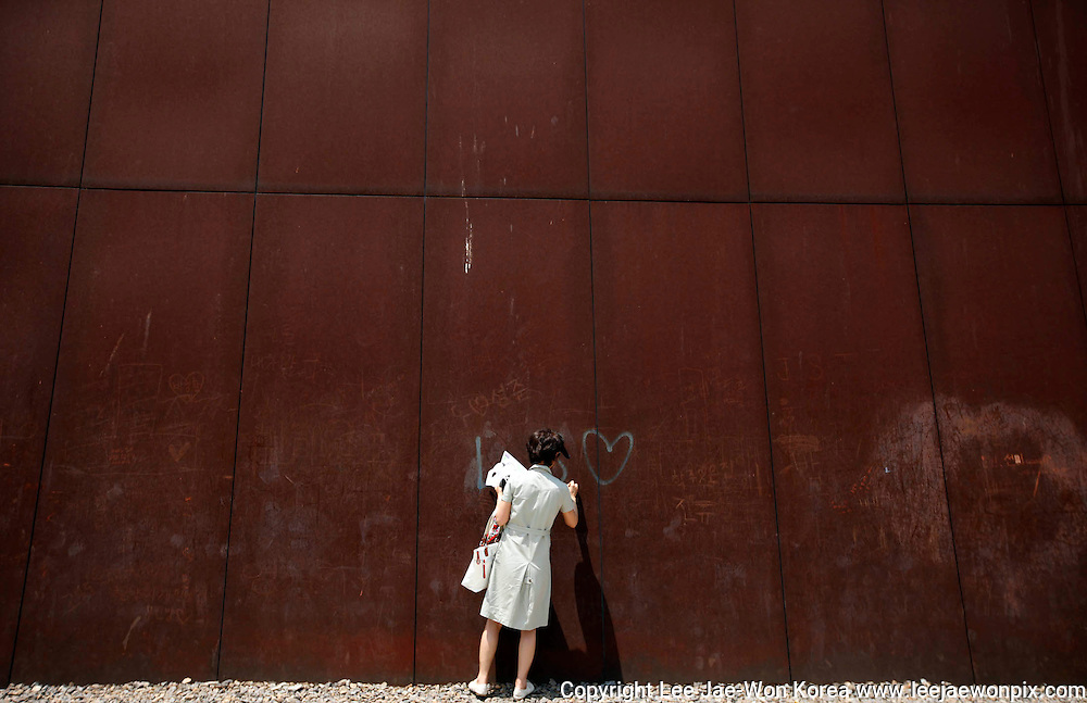 """A Catholic writes the Korean characters for """"Unification"""" on a steel wall during a mass for peace and reunification of the Korean peninsula at Imjingak Peace Park in Paju, near the demilitarised zone separating North Korea from South Korea, June 17, 2011. About 20,000 South Korean Catholics participated in the mass. /Lee Jae-Won"""