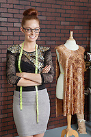 Portrait of an attractive female fashion designer standing arms crossed