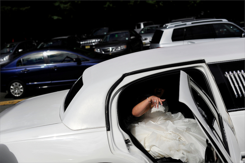 A bride steps out of the limousine prior to her wedding ceremony held at St. Gabriel the Archangel in Saddle River New Jersey.