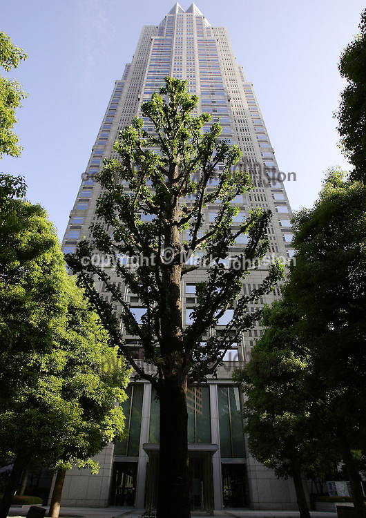 A carefully-manicured tree silhouetted by one of the Tokyo Metropolitan Government Office Buildings.
