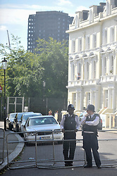 © Licensed to London News Pictures. 27/08/2017. London, UK. Police stand in front of a cordon surrounding the burned out shell of Grenfell Tower as members of the public pass by during Family Day at the Notting Hill Carnival.  Over one million revellers are expected to attend Europe's biggest street party which takes place over the Bank Holiday Weekend. Photo credit : Stephen Chung/LNP