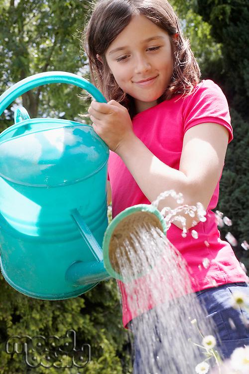 Girl (7-9) watering garden