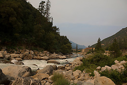 The Merced River flows through Yosemite National Park past the town of El Portal, California, USA on a hazy summer morning.