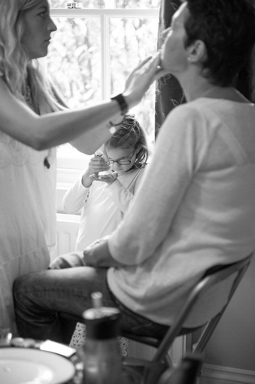 The daughter of the bride helps out whilst her Grandmother is made up.