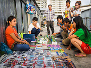 31 AUGUST 2013 - BANGKOK, THAILAND:       Construction workers look at cell phone accessories being sold by a vendor in front of the workers' dorm. The workers are building the Bhiraj Tower, a new office/retail complex under construction on Soi 35 Sukhumvit Road. It will be approximately 45 storeys when completed. The workers live in a complex of corrugated metal dorms about 1 kilometer from the construction site. They walk to and from the site every day.  PHOTO BY JACK KURTZ