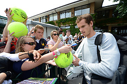 © London News Pictures.. 28/06/2013. Andrew Murray signs autographs following practice during the 2013 Wimbledon Lawn Tennis Championships. Andy Murray went on to win in the final becoming the first British male to win the tournament in 77 years. Photo credit: Mike King/LNP