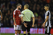 Referee Stephen Martin has words with Nottingham Forest midfielder Henri Lansbury (10) during the EFL Sky Bet Championship match between Nottingham Forest and Newcastle United at the City Ground, Nottingham, England on 2 December 2016. Photo by Jon Hobley.