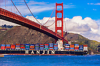 Container ship sailing through San Francisco Bay crossing under the Golden Gate Bridge, San Francisco, California USA