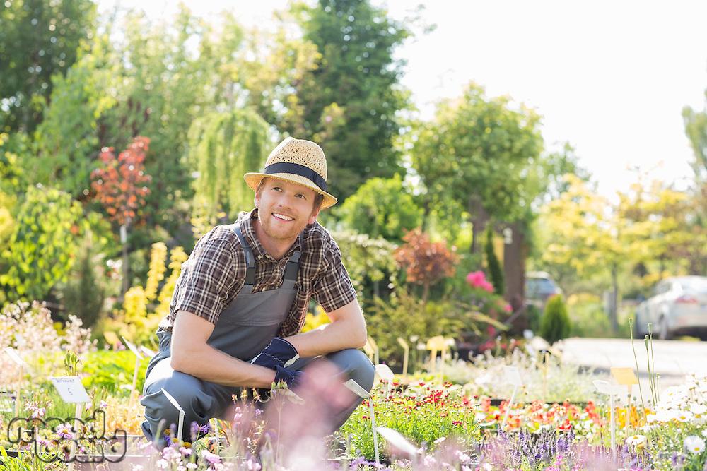 Man looking away while gardening at plant nursery