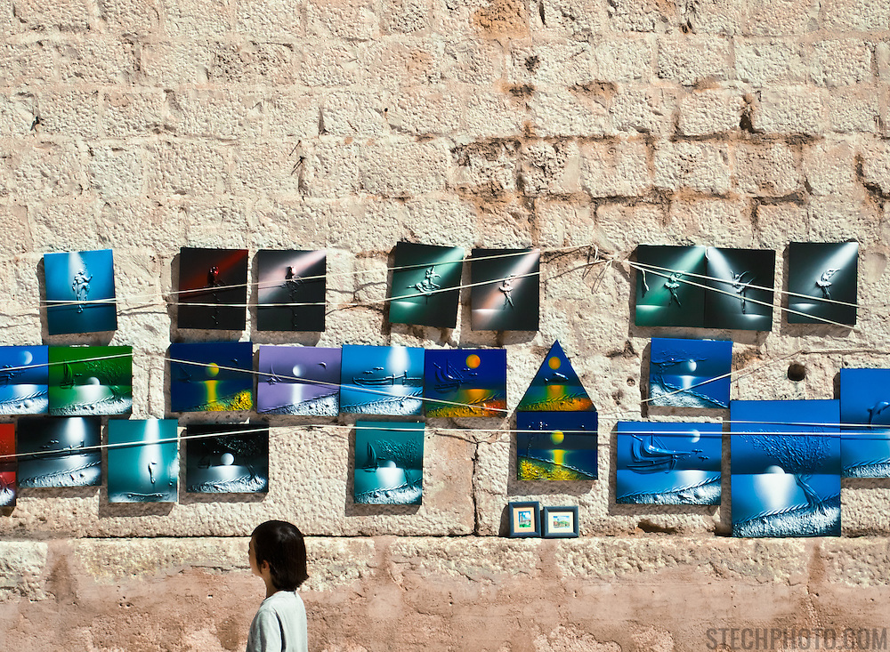 A passerby looking at some art for sale near the Roman Diocletian's Palace and the Cathedral of St. Duje in the heart of Split, Croatia.