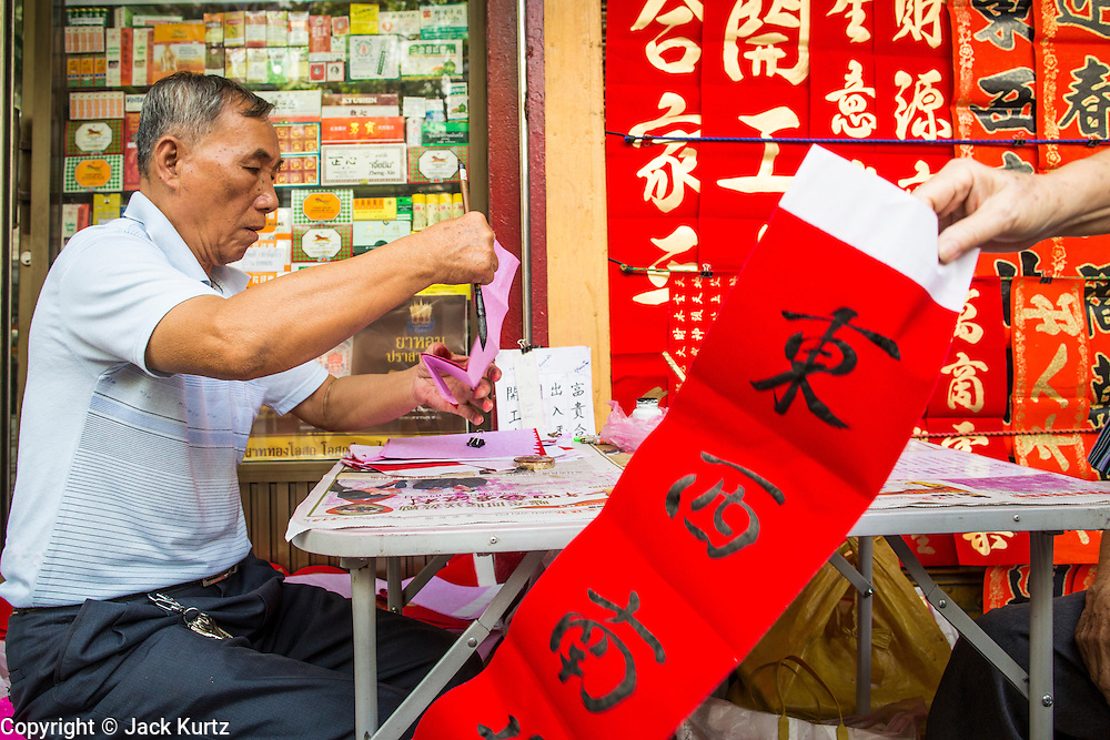 """22 JANUARY 2013 - BANGKOK, THAILAND:   A freshly written Chinese New Year greeting flutters in the breeze while a calligrapher works on another at his table on Charoen Krung Road in Bangkok's Chinatown district. Chinese New Year is not an official public holiday in Thailand, but it is one the biggest celebrations in the Bangkok, which has a large Chinese population. Chinese New Year is February 10 this year. It will be the """"Year of the Snake.""""    PHOTO BY JACK KURTZ"""