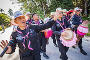 31 OCTOBER 2012 - YARANG, PATTANI, THAILAND: Thai soldiers dance as they escort villagers from Wat Kohwai on a procession to Yala for Ok Phansa. Ok Phansa marks the end of the Buddhist 'Lent' and falls on the full moon of the eleventh lunar month (October). It's a day of joyful celebration and merit-making. For the members of Wat Kohwai, in Yarang District of Pattani, it was a even more special because it was the first time in eight years they've been able to celebrate Ok Phansa. The Buddhist community is surrounded by Muslim villages and it's been too dangerous to hold the boisterous celebration because of the Muslim insurgency that is very active in this area. This the year the Thai army sent a special group of soldiers to secure the village and accompany the villagers on their procession to Yala, a city  about 20 miles away.   PHOTO BY JACK KURTZ