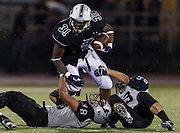 Cedar Ridge running back, Daniel Williams, gets brought down by Hendrickson's Nikolas Delacruz and Jason Slauenwhite.  The Hawks defeated the Raiders 35-28.