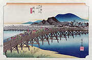 Bridge at the Okasaki station with porters and attendants carrying sedan chair and bundles.  From 'The Fifty-three Stations of the Tokaido Road' (1833-1834) by Utagawa Hiroshiga (1797-1858) Japanese Ukiyo-e artist.  Landscape Water