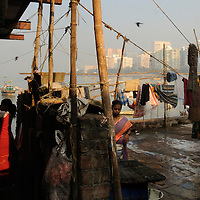 Women in a koliwada - fishing village -  a slum by Back Bay, belonging to the original inhabitants of the seven islands that became Mumbai, and now surrounded by some of India's most expensive real estate, in South Mumbai. Across the water is the business district of Nariman Point.