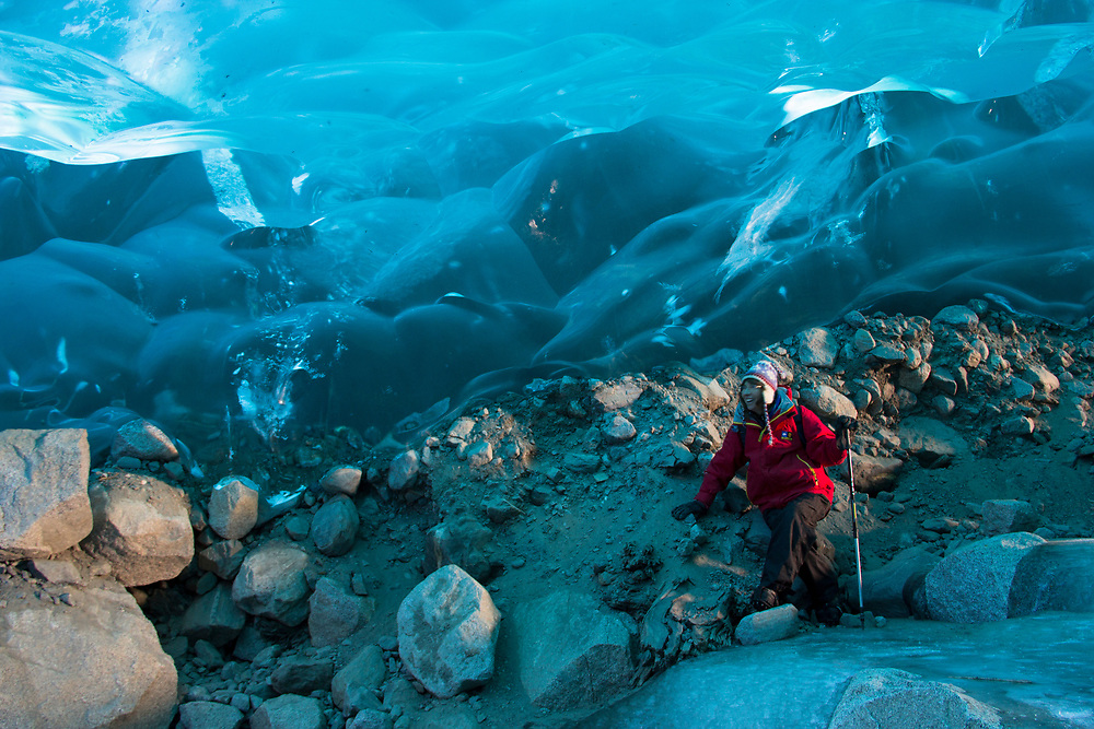 A hiker explores the blue ice cave beneath Mendenhall Glacier. MR