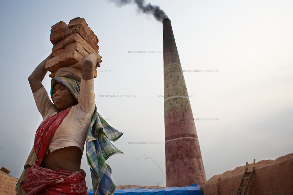 Migrant workers from the Adivasi (ie. NOT Musahar) community carry bricks from the oven to waiting trucks. This kiln is located close to Phulva Patti village in Kushinagar district. Many Musahar people from Maharajganj and Kushinagar districts in Uttar Pradesh find casual employment in local brick kilns. Other low caste and tribal communities, including Adivasis from the state of Jharkhand, work on the brick kilns. Income is based on piece-work. One Rupee is paid for every forty bricks carried from the kiln to waiting trucks. Sixteen Rupees (GB&pound;0.20) is paid for every 100 bricks moulded from the local clay. This moulding work is performed mainly by Musahar men who can expect to earn up to 160 Rupees (GB&pound;2.00) per day. Rates of pay are reduced in the winter. The day begins at 3am and finishes at 12 noon to avoid suffering the debilitating midday sun which dries the clay making it harder to handle. <br /> <br /> The Musahar community are one of India's most impoverished and marginalised groups. They are considered untouchable within the heavily stratified Hindu caste system. Most Musahar people reside in rural districts of Nepal and India's Uttar Pradesh, Madhya Pradesh and Bihar states where they are the victims of ingrained local prejudice and administrative indifference. Literacy levels in the community are as low as 2 percent and child malnutrition is common. The Musahar are poorly represented in both district-level government and the local administration. They suffer from low-self esteem and alcohol abuse is particularly common among men. An ongoing campaign for land-rights has provided an independent source of income for some but most Musahars continue to work as day-wage labourers for high caste land owners. Other campaigns have delivered successes in, for instance, the right to subsidised rations. But many of these victories are isolated and demonstrate the difficulties faced by Musahar people in raising a united voice against their suffering. The dominance of high cast