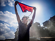 12 MARCH 2017 - BHAKTAPUR, NEPAL: Nepali men celebrate Holi with a Nepali flag in Bhaktapur. Holi, a Hindu religious festival, has become popular with non-Hindus in many parts of South Asia, as well as people of other communities outside Asia. The festival signifies the victory of good over evil, the arrival of spring, end of winter, and for many a festive day to meet others. Holi celebrations in Nepal are not as wild as they are in India.     PHOTO BY JACK KURTZ