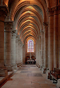Looking along one of the side aisles to a statue below a stained glass window, Laon Cathedral or the Cathedrale Notre-Dame de Laon, built 12th and 13th centuries in Gothic style, in Laon, Aisne, Picardy, France. The cathedral is listed as a historic monument. Picture by Manuel Cohen