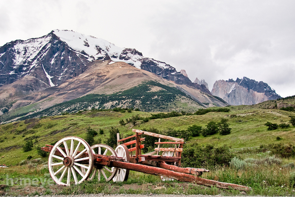 A rustic horse cart sits on a meadow with Monte Almirante and the peaks of Torres del Paine as a backdrop.  The view is typical of what one would find on the grounds of Hosteria Los Torres in Parque Nacional Torres del Paine in Chilean Patagonia.
