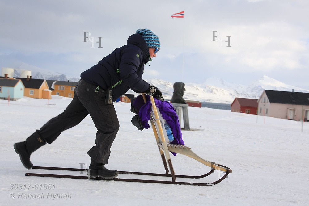 """Woman on kicksled, or """"spark,"""" glides along snowy road at the international science village of Ny-Alesund on Spitsbergen island in Kongsfjorden; Svalbard, Norway."""