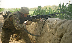 © licensed to London News Pictures.  22/08/2011 . Operation Zangal Haf, in the Helmand region of Afghanistan. During the operation the police seized a quantity of home made explosives from a compound. Pictured - Rifleman Daniel Meally looks over a wall as his patrol from A Company 1 Rifles come under heavy fire during a joint heli assault with the Afghan Uniformed Police. Photo credit Sergeant Alison Baskerville/LNP