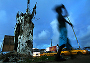 A Liberian boy walks past the remains of a shot up pillar on Bushroad Island, scene of intense fighting during the 2003 civil war in Monrovia, Liberia Thursday 13 October 2005.  As night falls Liberians go about their evening under dim lights from small generators as the city lacks electricity. Racked by civil war for more than 14 years Liberia finally got a taste of democracy as 1.3 million citizens head to the polls to vote in a new president.