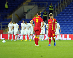 Aaron Ramsey (C) of Wales (Arsenal) and Sam Vokes of Wales (Burnley) cut dejected figures as Serbia celebrate  - Photo mandatory by-line: Joe Meredith/JMP - Tel: Mobile: 07966 386802 10/09/2013 - SPORT - FOOTBALL - Cardiff City Stadium - Cardiff -  Wales V Serbia- World Cup Qualifier