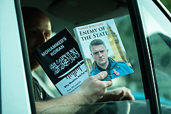 © Licensed to London News Pictures . 25/04/2019. Manchester, UK. A van driver holds copies of two bookes by Tommy Robinson as he drives past the event . Stephen Yaxley-Lennon (aka Tommy Robinson ) announces he is running for a seat in the European Parliament in North West England at a barbecue event on a green on a housing estate in Wythenshawe , South Manchester . Photo credit: Joel Goodman/LNP