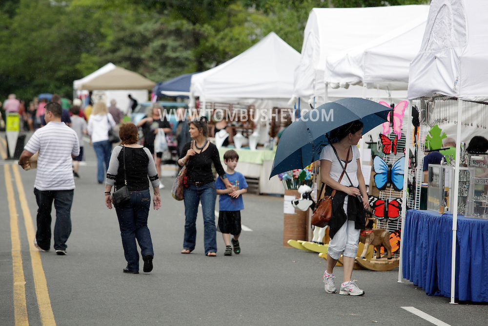 Sugar Loaf, New York - People walk through the rain while shopping on the closed street during the Sugar Loaf Spring Festival on May 21, 2011.