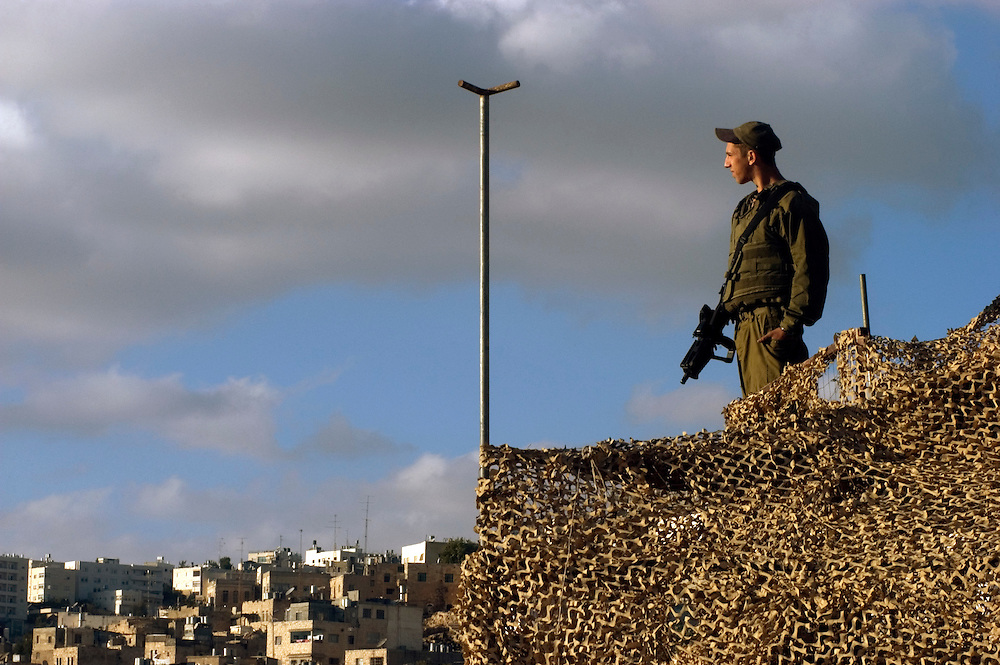 An Israeli soldier in a rooftop guard post overlooking the Jewish community in Hebron. Approximately 600 Jewish settlers live in the historic center of the city which has a Palestinian population of more than 160,000..Hebron, Israel. 08/11/2007.Photo © J.B. Russell/Blue Press