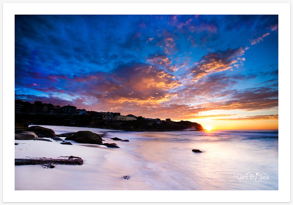 A spectacular autumn sunrise at Tamarama Beach. [Tamarama, NSW, Australia].<br /> <br /> To purchase please email orders@girtbyseaphotography.com quoting the image number PB106501, and your preferred print size. You will receive a quick reply recommending print media options to best suit your chosen image, plus an obligation-free quotation. Current standard size prices are published on the Pricing page.
