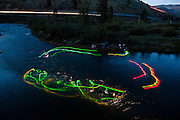 Noah Fraser, who organized this years world mystery championships squirt boats at night at the spot along the Truckee River near Reno, Nev., with glowsticks attached to his boat and paddle. Women's world mystery champion Claire O'hara can be seen paddling out in the background in this concept shoot designed to show what squirt boats do under water.