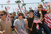 Crowd holding up American flags