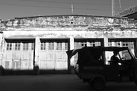 A rickshaw drives past  a warehouse in Mombasa, Kenya, in black and white