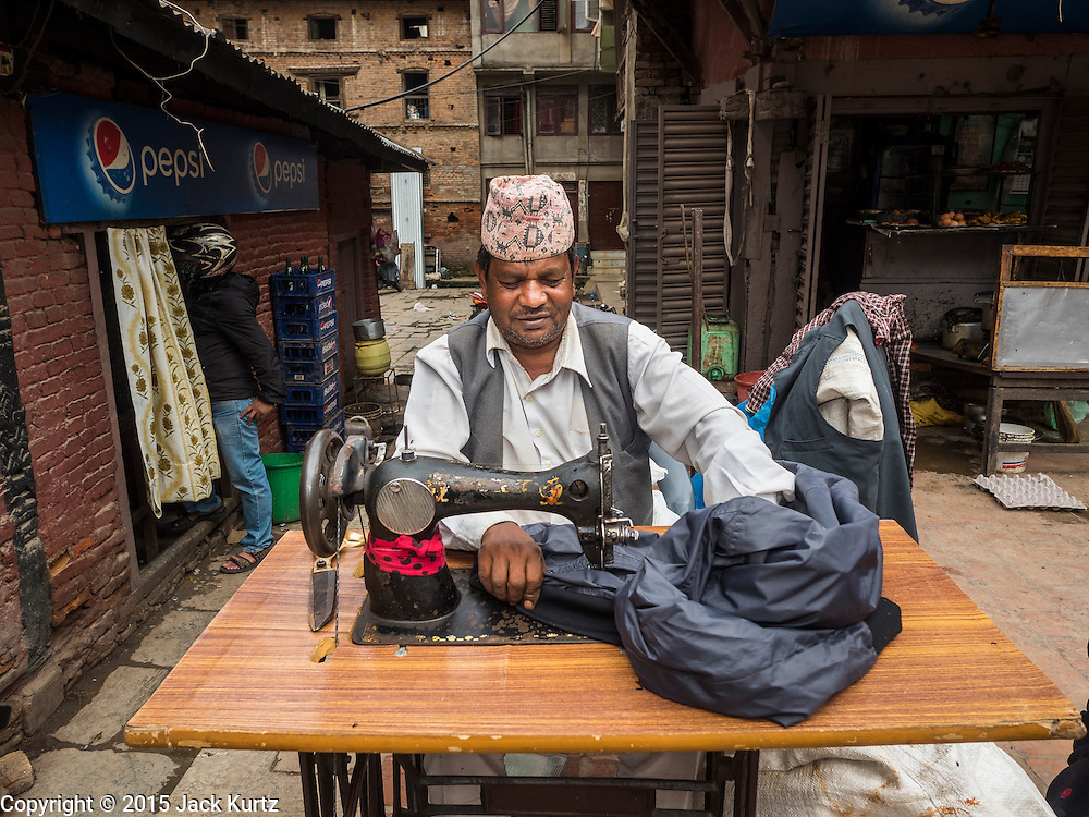 01 AUGUST 2015 - KATHMANDU, NEPAL: A Nepalese tailor works with his treadle sewing machine on a street corner in the Thamel neighborhood of Kathmandu.      PHOTO BY JACK KURTZ