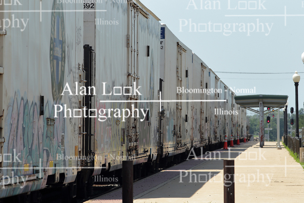 A freight train pulling box cars painted with railroad graffiti art travels past the Amtrak Depot in Galesburg Illinois