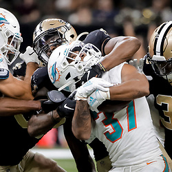 Aug 29, 2019; New Orleans, LA, USA; New Orleans Saints linebacker Darnell Sankey (44) and defensive back T.J. Green (36) tackle Miami Dolphins running back Myles Gaskin (37) during the second half of a preseason game at the Mercedes-Benz Superdome. Mandatory Credit: Derick E. Hingle-USA TODAY Sports