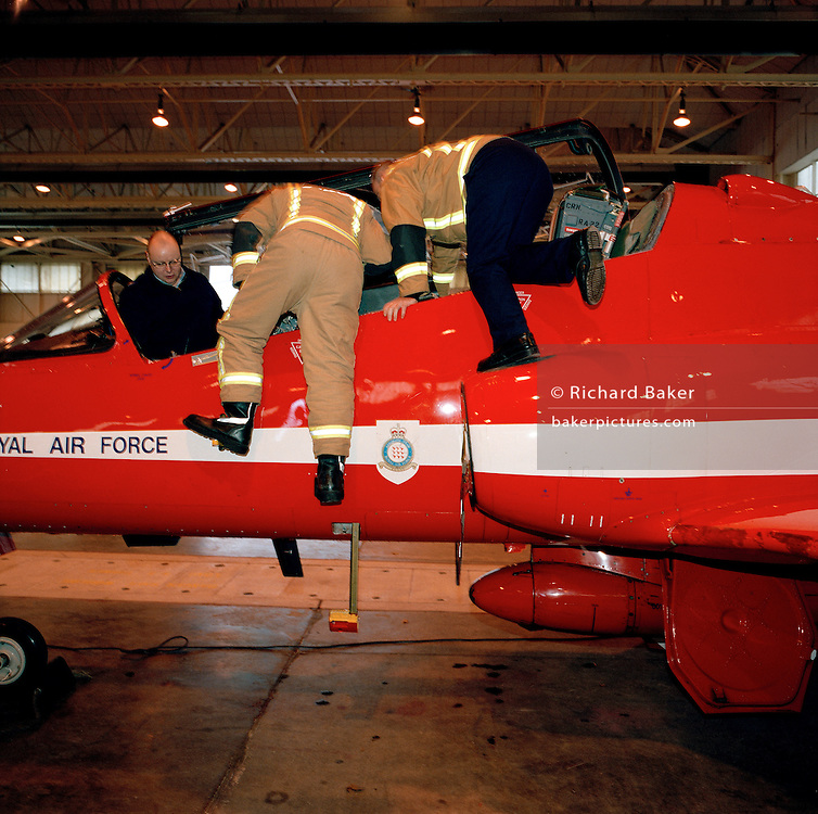 Local firefighters learn about the Hawk jet belonging to a Hawk jet in the hangar of the Red Arrows, Britain's RAF aerobatic team.