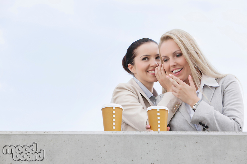 Happy businesswomen with disposable coffee cups sharing secrets against clear sky