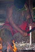 A polynesian man carves wood by a fire